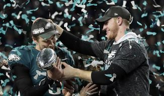 FILE - In this Sunday, Feb. 4, 2018, file photo, Philadelphia Eagles quarterback Carson Wentz, right, hands the Vincent Lombardi trophy to Nick Foles after winning the NFL Super Bowl 52 football game against the New England Patriots in Minneapolis. The Eagles aren't just celebrating their first championship since 1960 but also an abundance of talent at the position in franchise QB Carson Wentz and Super Bowl MVP Nick Foles. Should Wentz's recovery go well, the Eagles will have a huge bargaining chip to restock their roster. (AP Photo/Frank Franklin II, FIle) **FILE**