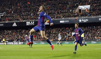 FC Barcelona's Philippe Coutinho, left, celebrates after scoring against Valencia during the Spanish Copa del Rey, semifinal, second leg, soccer match between FC Barcelona and Valencia at the Mestalla stadium in Valencia, Spain, Thursday Feb. 8, 2018. (AP Photo/Alberto Saiz)
