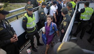 FILE - In this July 17, 2016 file photo, police stand guard as a Venezuelan woman crosses into Colombia through the Simon Bolivar bridge linking San Antonio del Tachira, Venezuela, with Cucuta, Colombia. President Juan Manuel Santos announced Thursday, Feb. 8, 2018, that more than 2,000 new officers will be dispatched to police the hundreds of unpaved, dirt road crossings migrants are using to enter Colombia illegally. Colombia will also stop issuing border cards that currently allow 1.5 million Venezuelans to temporarily enter the nation to purchase food and medicine. (AP Photo/Ariana Cubillos, File)