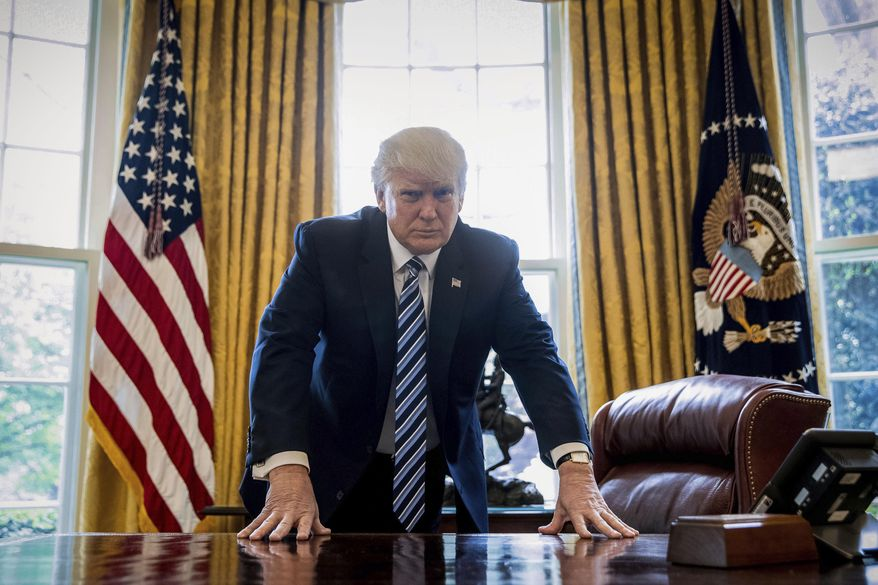 President Donald Trump poses at his desk in this Oval Office photo.