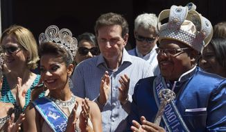 Flanked by Queen Jessica Maia, left, and the 2018 Carnival King Momo, Milton Junior, the Rio de Janeiro's Mayor Marcelo Crivella applauds at a ceremony marking the official start of Carnival in Rio de Janeiro, Brazil, Friday, Feb. 9, 2018. (AP Photo/Leo Correa)