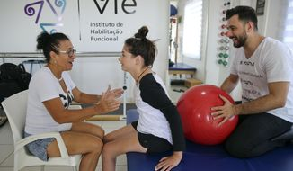 In this Feb. 1, 2018 photo, Brazil's Lais Souza attends a physiotherapy session, accompanied by her mother Odete Souza, left, in Ribeirao Preto, Brazil. The 29-year-old former Brazilian gymnast found herself paralyzed from the neck down after hitting a tree head on, during a freestyle ski practice in Utah for the 2014 Winter Olympics. (AP Photo/Andre Penner)