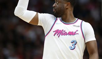 Miami Heat guard Dwyane Wade waves as he goes down court during the first half of the team's NBA basketball game against the Milwaukee Bucks, Friday, Feb. 9, 2018, in Miami. (AP Photo/Wilfredo Lee)