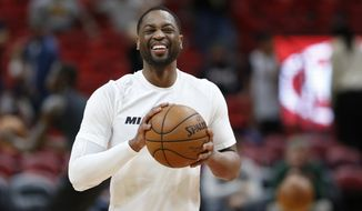 Miami Heat guard Dwyane Wade smiles as he warms up for the team's NBA basketball game against the Milwaukee Bucks, Friday, Feb. 9, 2018, in Miami. Wade was traded back to the Heat from the Cleveland Cavaliers on Thursday. (AP Photo/Wilfredo Lee)