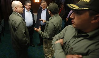 "Former rebel leaders of the Revolutionary Armed Forces of Colombia, FARC, Carlos Antonio Losada, left, Pablo Catatumbo, second from left, and Rodrigo Granda, third from left, talk to a police officers that makes part of their security team before a press conference, in Bogota, Colombia, Friday, Feb. 9, 2018. Leaders of the Common Alternative Revolutionary Force said Friday they have decided to halt all campaign activities until their safety can be assured. Former guerrilla commander Rodrigo Londono, better known by his alias Timochenko, is running for president of Colombia and has been confronted by angry mobs hurling eggs and shouting ""Murderer!"" since launching his campaign. (AP Photo/Fernando Vergara)"