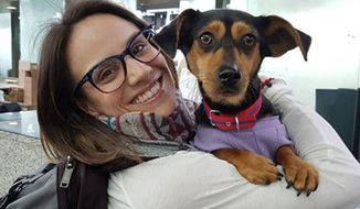 In this undated photo provided by Free Korean Dogs, Canadian figure skater Meagan Duhamel poses with her dog Moo-tae, right, in South Korea. Duhamel already has one life-changing souvenir from South Korea, and it's not a medal. The Olympic pairs skater rescued a puppy from the Korean dog meat trade while competing in Pyeongchang last year, and she's helping organize more adoptions while skating there at this year's games. (EK Park/Free Korean Dogs via AP)