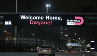 A sign at the entrance of Miami International Airport welcomes back to the Miami Heat Dwyane Wade, who was traded to the Heat by the Cleveland Cavaliers on Thursday, Feb. 8, 2018. (AP Photo/Wilfredo Lee)