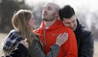 In this March 14, 2014, file photo, Michael Behenna, center, is embraced by his brother Brett and girlfriend Shannon Wahl following his release from prison in Leavenworth, Kan. Behenna, who was convicted of killing an Iraqi prisoner, served five years of his 15-year sentence for unpremeditated murder in a combat zone. Oklahoma's Attorney General Mike Hunter is urging President Donald Trump to issue a pardon to Behenna. (Sarah Phipps/The Oklahoman via AP)