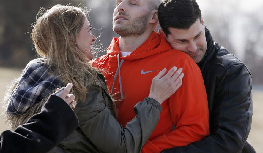 FILE - In this March 14, 2014, file photo, Michael Behenna, center, is embraced by his brother Brett and girlfriend Shannon Wahl following his release from prison in Leavenworth, Kan. Behenna, who was convicted of killing an Iraqi prisoner, served five years of his 15-year sentence for unpremeditated murder in a combat zone. Oklahoma's Attorney General Mike Hunter is urging President Donald Trump to issue a pardon to Behenna. (Sarah Phipps/The Oklahoman via AP)