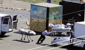 FILE - In this Oct. 2, 2017, file photo, investigators load bodies from the scene of a mass shooting at a music festival near the Mandalay Bay resort and casino on the Las Vegas Strip in Las Vegas. An autopsy found Las Vegas shooter Stephen Paddock had anti-anxiety drugs in his system but was not under the influence of them and was otherwise healthy.  A Las Vegas judge has ordered The Associated Press and Las Vegas Review-Journal to return copies of a redacted autopsy of an off-duty police officer killed in the deadliest mass shooting in modern U.S. history, Friday, Feb. 9, 2018. (AP Photo/Chris Carlson, file)