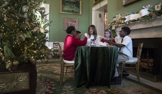 FILE - In this Monday, Nov. 27, 2017 file photo, first lady Melania Trump visits with children in the Green Room among the 2017 holiday decorations at the White House in Washington. On Friday, Feb. 9, 2018, The Associated Press has found that stories circulating on the internet that Melania Trump hired an exorcist to cleanse the White House of Obama demons are untrue. (AP Photo/Carolyn Kaster)