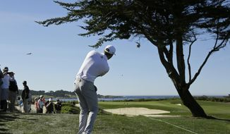 Dustin Johnson follows his chip shot to the 13th green of the Monterey Peninsula Country Club Shore Course during the second round of the AT&T Pebble Beach National Pro-Am golf tournament Friday, Feb. 9, 2018, in Pebble Beach, Calif. (AP Photo/Eric Risberg)