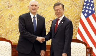 U.S. Vice President Mike Pence, left, shakes hands with South Korean President Moon Jae-in prior to their meeting at the presidential office Blue House in Seoul Thursday, Feb. 8, 2018. (Kim Hee-chul/Pool Photo via AP)