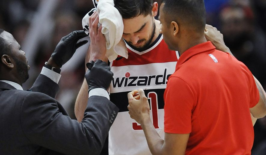 Washington Wizards' Tomas Satoransky, of the Czech Republic, is tended to after being injured when fouled by Chicago Bulls' Bobby Portis during the final minutes of an NBA basketball game Saturday, Feb. 10, 2018, in Chicago. Washington won 101-90. (AP Photo/Paul Beaty)