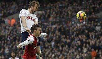 Tottenham Hotspur's Harry Kane, top, leaps above Arsenal's Laurent Koscielny as he scores the opening goal of the game during the English Premier League soccer match between Tottenham Hotspur and Arsenal at Wembley stadium in London, Saturday, Feb. 10, 2018. (AP Photo/Matt Dunham)