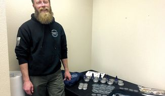 In this Jan. 31, 2018, photo, Permafrost Beards owner Nick Adkins poses next to his products in Fairbanks, Alaska. Permafrost beards offers a number of products to Alaskans needing to take good care of their facial hair in the harsh climate of the state, as well as the rest of the world. (Dorothy Chomicz/Fairbanks Daily News-Miner via AP)