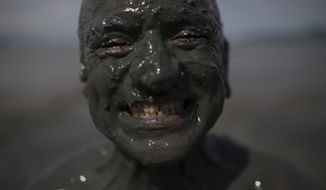 "A mud covered reveler poses for a picture during the traditional ""Bloco da Lama"" or ""Mud Block"" carnival party in Paraty, Brazil, Saturday, Feb. 10, 2018. Hundreds of revelers wrestled, tackled each other and threw chunks of gunk Saturday while shaking it to samba and reggaeton at a Carnival beach party where clothes were optional but the mud was not. (AP Photo/Leo Correa)"
