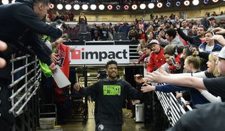 CORRECTS YEAR TO 2018 - Former Chicago Bulls player Jimmy Butler, center, greets fans as he heads onto the court as a member of the Minnesota Timberwolves before an NBA basketball game  against the Bulls, Friday, Feb. 9, 2018, in Chicago. (AP Photo/Matt Marton)
