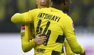 Dortmund's Michy Batshuayi celebrates with Dortmund's Marco Reus after scoring the opening goal during the German Bundesliga soccer match between Borussia Dortmund and Hamburger SV in Dortmund, Germany, Saturday, Feb. 10, 2018. (AP Photo/Martin Meissner)