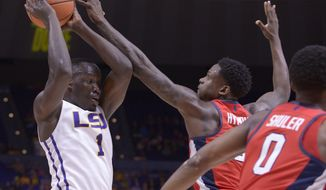 LSU forward Duop Reath (1) works to move the ball past Mississippi forward Marcanvis Hymon (2) and guard Devontae Shuler (0) during the first half of an NCAA college basketball game Saturday, Feb. 10, 2018, in Baton Rouge, La. (Hilary Scheinuk/The Advocate via AP)