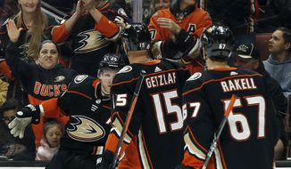 Anaheim Ducks right wing Corey Perry, left, celebrates his goal against the Edmonton Oilers with center Ryan Getzlaf, center, and center Rickard Rakell, of Sweden, during the second period of an NHL hockey game in Anaheim, Calif., Friday, Feb. 9, 2018. (AP Photo/Alex Gallardo)