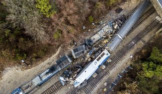 The wreckage of an Amtrak train, bottom, and a CSX freight train lie next to the tracks in Cayce, SC., on Sunday, Feb. 4, 2018. The trains collided in the early morning darkness Sunday, killing the Amtrak conductor and engineer, and injuring more than 100 passengers. (AP Photo/Jeff Blake)