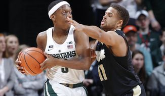 Michigan State's Cassius Winston, left, is pressured by Purdue's P.J. Thompson during the first half of an NCAA college basketball game, Saturday, Feb. 10, 2018, in East Lansing, Mich. (AP Photo/Al Goldis)