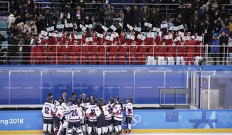 North Korea supporters, top, wave the Korean unification flag as players of combined Koreas gather at the end of a women's hockey game against Switzerland at the 2018 Winter Olympics in Gangneung, South Korea, Saturday, Feb. 10, 2018. (AP Photo/Felipe Dana)