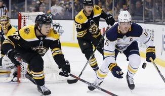 Boston Bruins' Charlie McAvoy (73) battles Buffalo Sabres' Jack Eichel (15) for the puck during the first period of an NHL hockey game in Boston, Saturday, Feb. 10, 2018. (AP Photo/Michael Dwyer)