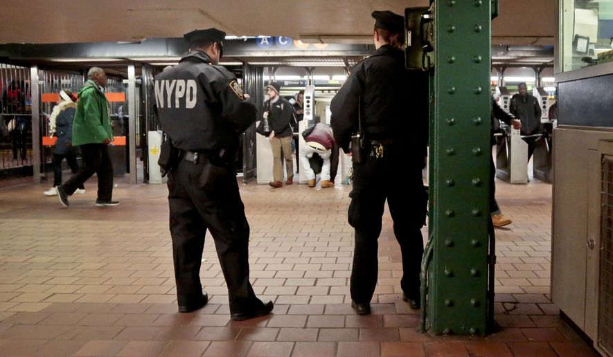 In this March 3, 2016 photo, New York City police officers observe commuters using turnstiles at a Harlem subway station in New York. New York City police and transit officials say a new policy not to prosecute subway fare jumpers could embolden criminals and cause chaos. But Manhattan prosecutors say their policy that took effect this month makes sense because two-thirds of those arrested in for the crime in the borough had no prior convictions. (AP Photo/Bebeto Matthews)