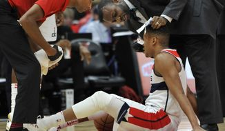 Washington Wizards' Tim Frazier received attention after being injured during the first half of the team's NBA basketball game against the Chicago Bulls on Saturday, Feb. 10, 2018, in Chicago. (AP Photo/Paul Beaty) **FILE**