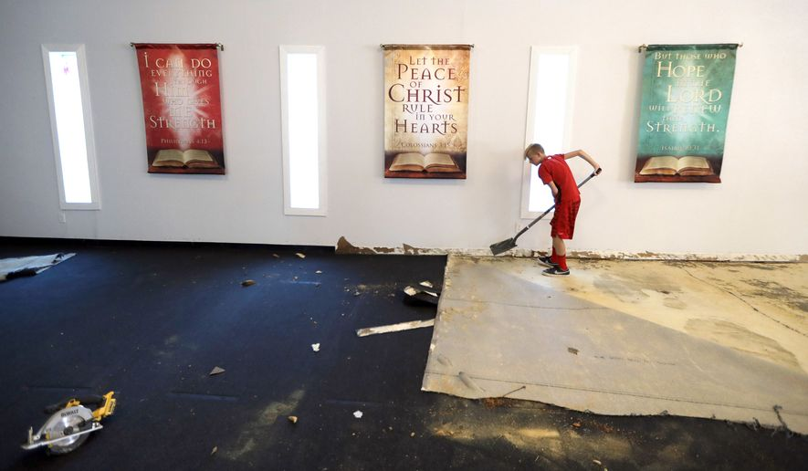 Joshua Miller, 12, helps remove carpet damaged by floodwaters inside his father's church, Messiah Mission Fellowship, in the aftermath of Hurricane Harvey Saturday, Sept. 2, 2017, in Houston. (AP Photo/David J. Phillip)