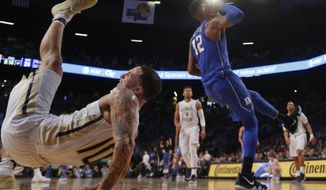 Georgia Tech guard Jose Alvarado (10) falls to the floor after battling Duke forward Javin DeLaurier (12) during an NCAA college basketball game Sunday, Feb. 11, 2018, in Atlanta. Alvarado injured his arm and left the game. (AP Photo/John Bazemore)