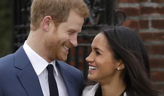 In this file photo dated  Monday Nov. 27, 2017, Britain's Prince Harry and his fiancee Meghan Markle pose for photographers in the grounds of Kensington Palace in London, following the announcement of their engagement. (AP Photo/Matt Dunham, File)