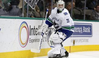 Vancouver Canucks goaltender Jacob Markstrom (25) protects the puck against the Dallas Stars during the first period of an NHL hockey game in Dallas, Sunday, Feb. 11, 2018. (AP Photo/Michael Ainsworth)