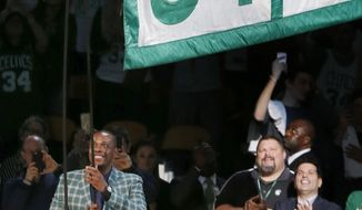 Former Boston Celtics Paul Pierce, left, raises a banner during a ceremony to retire his number following an NBA basketball game against the Cleveland Cavaliers in Boston, Sunday, Feb. 11, 2018. (AP Photo/Michael Dwyer)