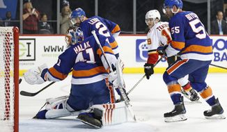 New York Islanders goaltender Jaroslav Halak (41) of Slovakia, and teammates Islanders defensemen Nick Leddy (2) and Johnny Boychuk (55) watch as Matthew Tkachuk's game-winning goal sails in for a score during the third period of an NHL hockey game in New York, Sunday, Feb. 11, 2018. The Flames defeated the Islanders on Tkachuk's goal. Tkachuck (19) is between the Islanders trio. (AP Photo/Kathy Willens)