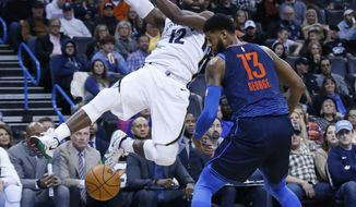 Oklahoma City Thunder forward Paul George (13) knocks the ball away from Memphis Grizzlies guard Tyreke Evans (12) in the first half of an NBA basketball game in Oklahoma City, Sunday, Feb. 11, 2018. (AP Photo/Sue Ogrocki)