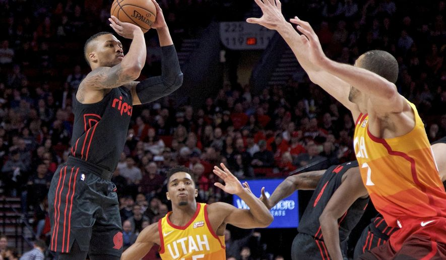 Portland Trail Blazers guard Damian Lillard, left, shoots over Utah Jazz guard Donovan Mitchell, center and center Rudy Gobert, right, during the first half of an NBA basketball game in Portland, Ore., Sunday, Feb. 11, 2018. (AP Photo/Craig Mitchelldyer)