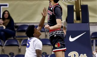 Louisville's Anas Mahmoud, top, blocks a shot by Pittsburgh's Marcus Carr (5) during the first half of an NCAA college basketball game, Sunday, Feb. 11, 2018, in Pittsburgh. (AP Photo/Keith Srakocic)