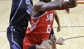 Houston Rockets center Clint Capela (15) shoots as Dallas Mavericks guard Dennis Smith Jr., bottom and forward Doug McDermott, left, defend during the first half of an NBA basketball game, Sunday, Feb. 11, 2018, in Houston. (AP Photo/Eric Christian Smith)