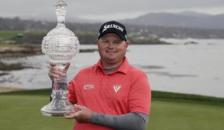 Ted Potter Jr. poses with his trophy on the 18th green of the Pebble Beach Golf Links after winning the AT&T Pebble Beach National Pro-Am golf tournament Sunday, Feb. 11, 2018, in Pebble Beach, Calif. (AP Photo/Eric Risberg)