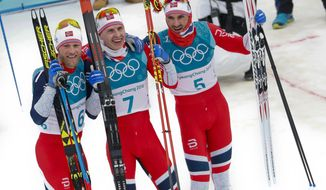 Gold medal winner Simen Hegstad Krueger, of Norway, is flanked by silver medal winner Martin Johnsrud Sundby, of Norway, left, and bronze medal winner Hans Christer Holund, of Norway, after the men's 15km/15km skiathlon cross-country skiing competition at the 2018 Winter Olympics in Pyeongchang, South Korea, Sunday, Feb. 11, 2018. (AP Photo/Matthias Schrader)