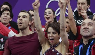 Meagan Duhamel and Eric Radford of Canada react with their teammates as they watch their scores posted following their performance in the team event pair skating in the Gangneung Ice Arena at the 2018 Winter Olympics in Gangneung, South Korea, Sunday, Feb. 11, 2018. (AP Photo/Julie Jacobson)