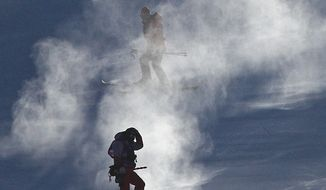 Course crew are shrouded in snow after the women's giant slalom was postponed due to high winds on Monday. (ASSOCIATED PRESS)