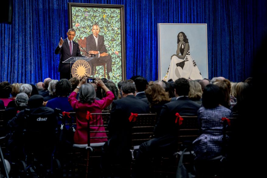 Former President Barack Obama, left, speaks at the unveiling ceremony for the Obama's official portraits at the Smithsonian's National Portrait Gallery, Monday, Feb. 12, 2018, in Washington. Obama's portrait was painted by Artist Kehinde Wiley, and Michelle Obama's portrait was painted by Artist Amy Sherald. (AP Photo/Andrew Harnik)