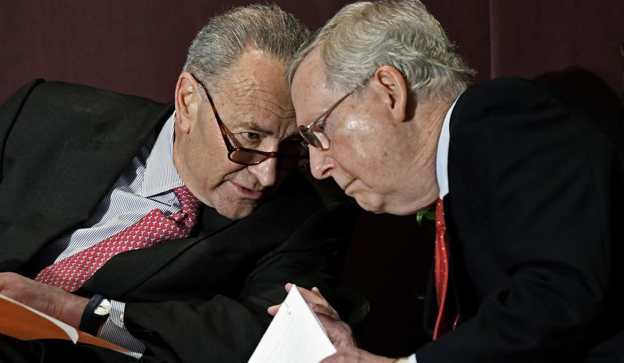 Senate Minority Leader Charles Schumer, D-N.Y., left, leans in to speak to Senate Majority Leader Mitch McConnell, R-Ky., before his speech at the McConnell Center's Distinguished Speaker Series Monday, Feb. 12, 2018, in Louisville, Ky. (AP Photo/Timothy D. Easley)