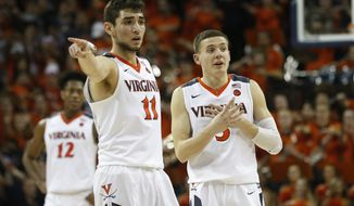 Virginia guard Ty Jerome (11) and Virginia guard Kyle Guy (5) look sot he bench during the second half of an NCAA college basketball game in Charlottesville, Va., Saturday, Feb. 10, 2018. Virginia Tech won the game 61-60 in overtime. (AP Photo/Steve Helber)