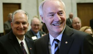 Gov. Asa Hutchinson prepares to speak to a joint session of legislators Monday, Feb. 12, 2018, at the state Capitol in Little Rock, Ark. Behind him is Arkansas Treasurer Dennis Milligan. The governor told lawmakers that, next year, he would like them to cut the state's top income tax rate from 6.9 percent to 6 percent, a move that would save Arkansas' top earners $180 million annually. (AP Photo/Kelly P. Kissel)