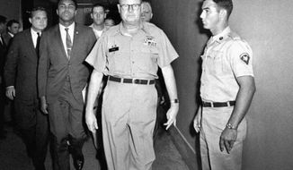 FILE - In this April 28, 1967 file photo, heavyweight boxing champion Muhammad Ali is escorted from the Armed Forces Examining and Entrance Station in Houston by Lt. Col. J. Edwin McKee, commandant of the station, after Ali refused Army induction. Ali never spent a day in prison for his actions even though he was sentenced to serve five years for draft evasion before the Supreme Court overturned his case on a technicality. But many black athletes have paid when taking a stand, or a knee,  for speaking out for social or political change. Ali lost the heavyweight title and spent three years in forced exile from the ring. (AP Photo/File)